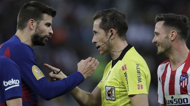 Barcelona's Gerard Pique, left, discusses with the referee during the Spanish Super Cup semifinal soccer match between Barcelona and Atletico Madrid at King Abdullah stadium in Jiddah, Saudi Arabia, Friday, Jan. 10, 2020. (AP Photo/Amr Nabil)