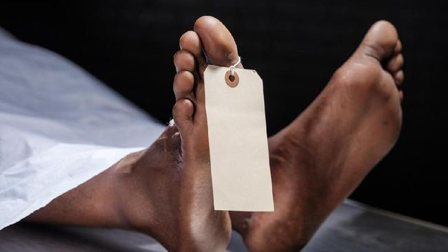 A close-up of the foot of a dead person in a morgue. A blank tag is attached to the toe.