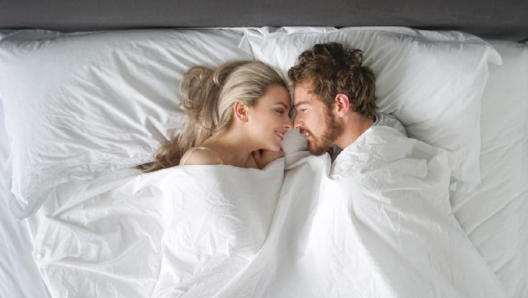 Couple is hugging and taking selfie on the bed in the morning