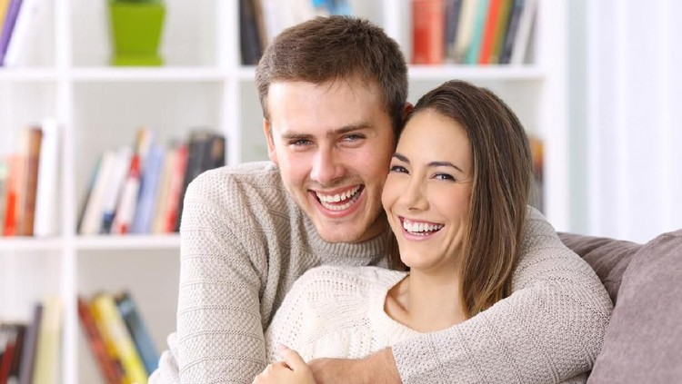 Front view portrait of a happy couple with perfect smile looking at you sititng on a couch in the living room at home in winter