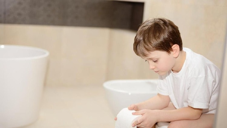 Little 7 years old boy sitting on toilet. Holding white toilet paper