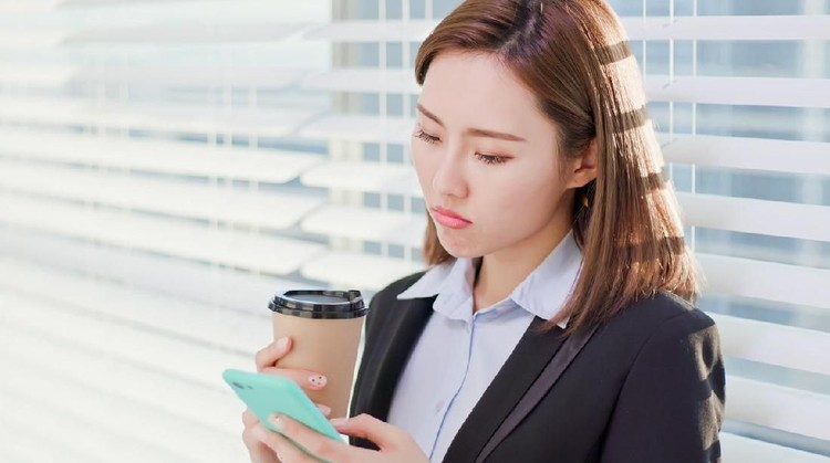 business woman feel depress and use smart phone while drinking coffee in the office