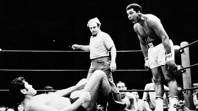 US boxer Muhammad Ali, born Cassius Marcellus Clay Jr. on January 17, 1942, three-time World Heavyweight Champion and winner of an Olympic Light-heavyweight gold medal, shouts at a Japanese wrester during an exhibition fight in Tokyo, 01 July 1976. AFP PHOTO (Photo by AFP)