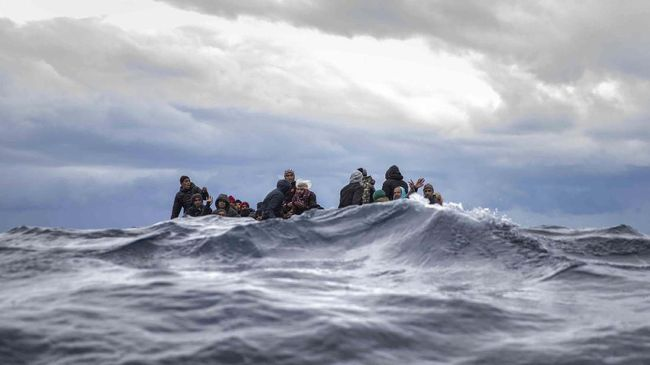 Men from Morocco and Bangladesh sit in an overcrowded wooden boat as aid workers of the Spanish NGO Open Arms approach them in the Mediterranean Sea, international waters, off the Libyan coast, Friday, Jan. 10, 2020. (AP Photo/Santi Palacios)