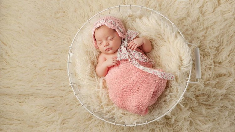A portrait of a five week old newborn baby girl wearing a pink bonnet and sleeping in a wire basket. Shot from overhead.