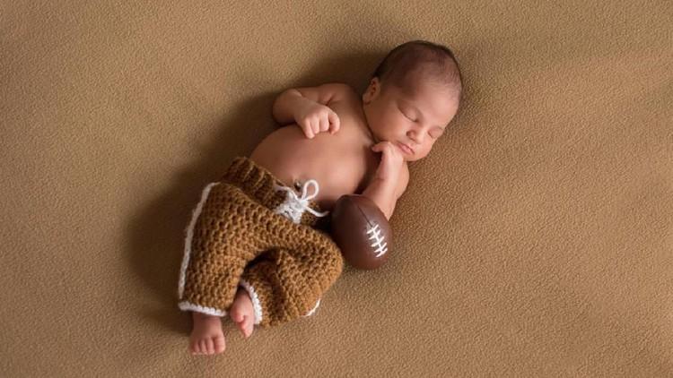 A sleeping, nine day old newborn baby boy wearing crocheted football uniform pants.