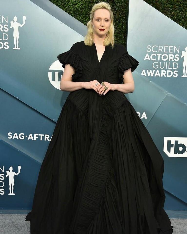 Gwendoline Christie,mengenakan gaun hitam panjang yang terlihat kebesaran untuknya.