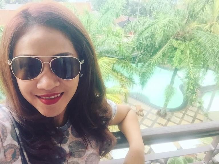 Fanni Aminadia berpose mengenakan kacamata hitam dengan latar belakang pemandangan yang indah.