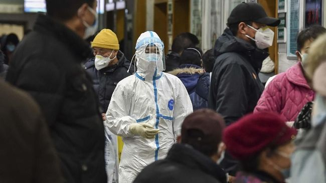 A medical staff member (C) wearing protective clothing to help stop the spread of a deadly virus which began in the city, walks at the Wuhan Red Cross Hospital in Wuhan on January 24, 2020. - Chinese authorities rapidly expanded a mammoth quarantine effort aimed at containing a deadly contagion on January 24 to 13 cities and a staggering 41 million people, as nervous residents were checked for fevers and the death toll climbed to 26. (Photo by Hector RETAMAL / AFP)
