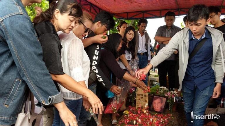 Usai dimakamkan para keluarga pun menaburkan bunga di atas makan Johny Indo.