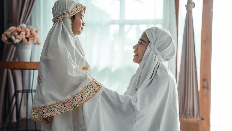 muslim mother help her young daughter to put the scarf on before pray