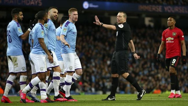 Referee Kevin Friend gestures to Manchester City players appealing for a penalty shot during the English League Cup semifinal second leg soccer match between Manchester City and Manchester United at Etihad stadium in Manchester, England, Wednesday, Jan. 29, 2020. (AP Photo/Dave Thompson)