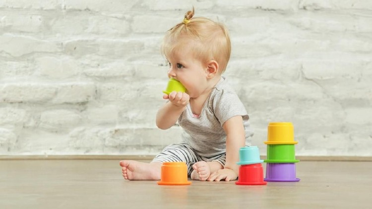Baby girl playing on the floor with plastic educational   cups, early learning concept