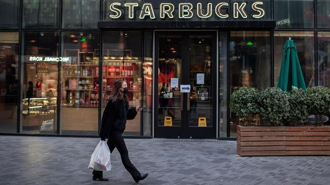 A woman, wearing a protective facemask, walks past a Starbucks coffee shop (back) in Beijing on January 30, 2020. - The World Health Organization, which initially downplayed the severity of a disease that has now killed 170 nationwide, warned all governments to be