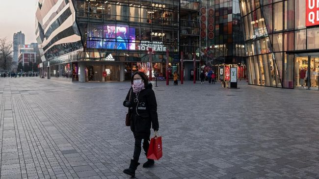 A woman wearing a protective facemask walks past a nearly-deserted shopping mall in Beijing on February 3, 2020. - A virus similar to the SARS pathogen has killed more than 300 people in China and spread around the world since emerging in a market in the central Chinese city of Wuhan. (Photo by NICOLAS ASFOURI / AFP)
