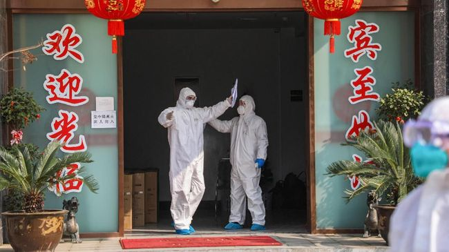This photo taken on February 3, 2020 shows a medical staff member (L) being disinfected by a colleague before leaving a quarantine zone converted from a hotel in Wuhan, the epicentre of the new coronavirus outbreak, in China's central Hubei province. - The number of total infections in China's coronavirus outbreak has passed 20,400 nationwide with 3,235 new cases confirmed, the National Health Commission said on February 4. (Photo by STR / AFP) / China OUT