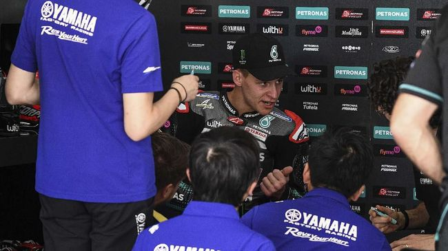 Petronas Yamaha SRT's French rider Fabio Quartararo (C) speaks with team members during the first day of the pre-season MotoGP winter test at the Sepang International Circuit in Sepang on February 7, 2020. (Photo by Mohd RASFAN / AFP)