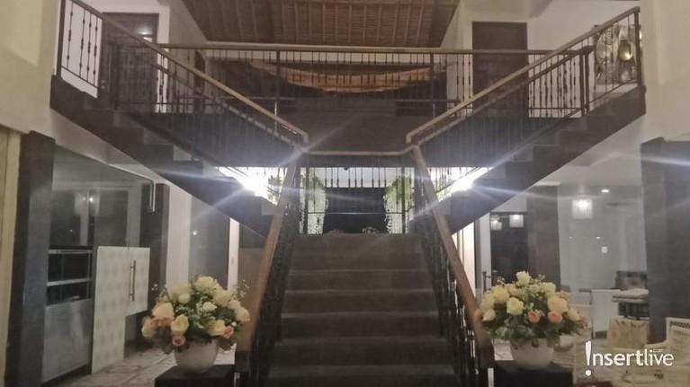 Di depan pintu masuk yang dihiasi bunga, terdapat sebuah tangga yang direncanakan akan digunakan Vanessa dan Bibi untuk turun dan menyambut para tamu.