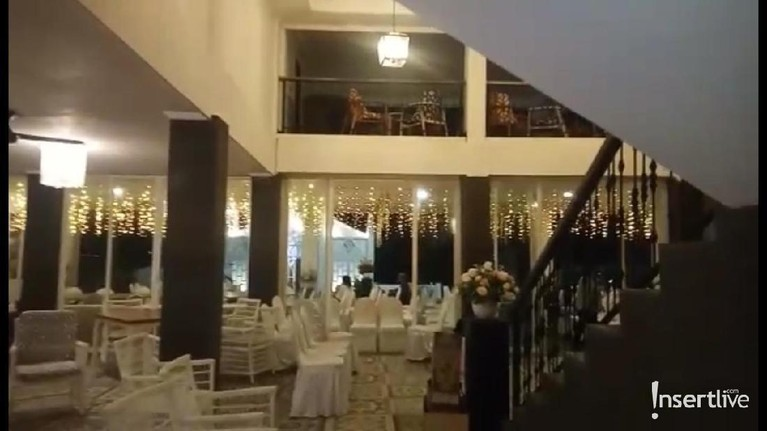 Melirik ke dalam, aula megah tersebut sudah diisi dengan bangku-bangku serba putih dan dekorasi yang juga putih.
