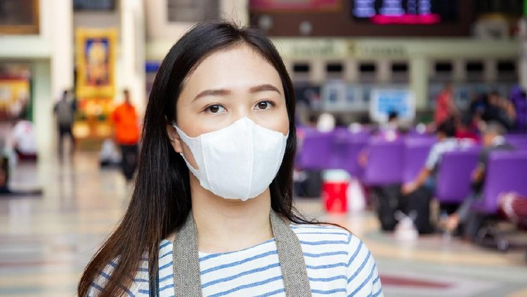 Asian woman masked a protective mask in public area close up.