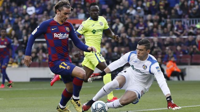 Barcelona's Antoine Griezmann, left, prepares to shoot past Getafe's goalkeeper David Soria to score his side's opening goal during a Spanish La Liga soccer match between Barcelona and Getafe at the Camp Nou stadium in Barcelona, Spain, Saturday Feb. 15, 2020. (AP Photo/G.Garin)