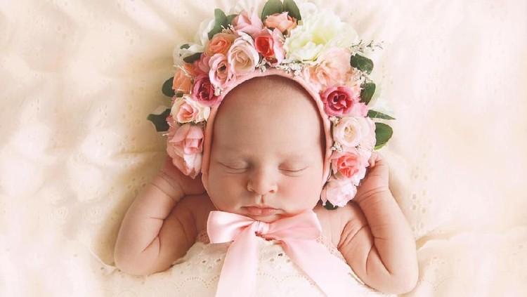 A newborn baby girl, fast asleep, wears a bonnet of flowers.