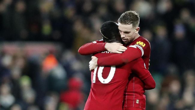Liverpool's Sadio Mane, left, and Liverpool's Jordan Henderson celebrate at the end of the English Premier League soccer match between Norwich City and Liverpool at Carrow Road Stadium in Norwich, England, Saturday, Feb. 15, 2020. (AP Photo/Frank Augstein)