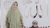 Ingin pergi ke pengajian bersama anak? Coba tampil serasi dengan si kecil. Gaya hijab syar'i a la Oki Setiana Dewi dengan pilihan gamis dan kerudung instan serupa. Pilihan khimar layering memang bisa menambah kesan stylish, Bun. (Foto: Instagram @okisetianadewi)