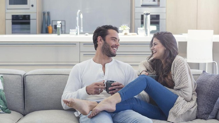 Shot of a smiling young couple talking together while relaxing on a beanbag sofa at home