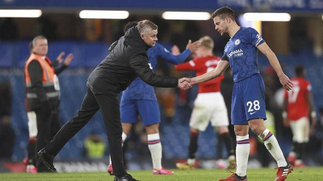 Manchester United's manager Ole Gunnar Solskjaer, left, shakes the hand of Chelsea's Cesar Azpilicueta after their English Premier League soccer match at Stamford Bridge in London, England, Monday, Feb. 17, 2020. (AP Photo/Ian Walton)