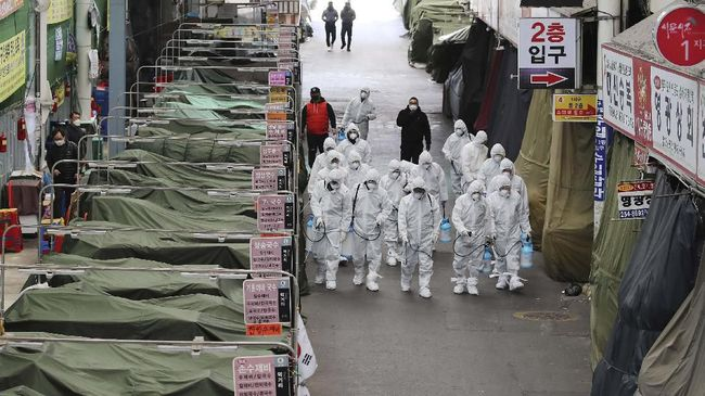 Workers wearing protective gear spray disinfectant as a precaution against the COVID-19 coronavirus in a local market in Daegu, South Korea, Sunday, Feb. 23, 2020. South Korea's president has put the country on its highest alert for infectious diseases and says officials should take