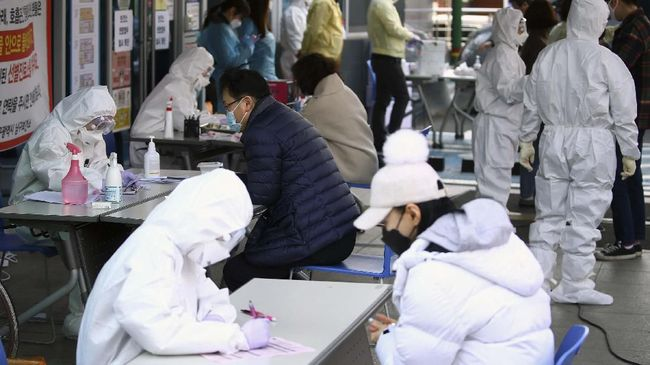 People suspected of being infected with the new coronavirus talk with medial center workers to receive tests in Daegu, South Korea, Friday, Feb. 21, 2020. South Korea reported 100 new virus cases Friday, bringing the country's total to 204, many of them clustered around a southeastern city, and raising fears that the outbreak is getting out of control. (Kim Hyun-tae/Yonhap via AP)