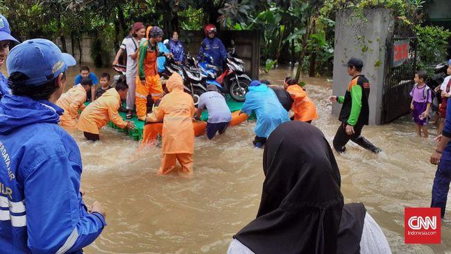 Warga dan petugas UPK memanfaatkan sebuah kubus yang dijadikan getek (rakit) untuk mengangkut motor milik pengendara yang terjebak banjir di Cipayung, Jakarta.