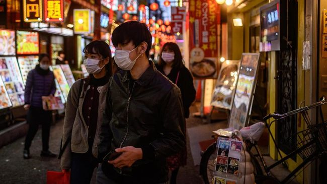 This photo taken on February 23, 2020 shows pedestrians wearing face masks as they walk in the Chinatown district in Yokohama. - Japan has more than 130 cases of the COVID-19 coronavirus and four have died. Three of those deaths were passengers who had been on the cruise ship Diamond Princess, quarantined off in Yokohama, where the number of infections is now at 630. (Photo by Philip FONG / AFP)