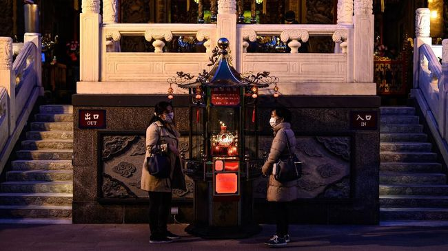 This photo taken on February 23, 2020 shows people wearing face masks as they gather at the Guandi Temple in the Chinatown district in Yokohama. - Japan has more than 130 cases of the COVID-19 coronavirus and four have died. Three of those deaths were passengers who had been on the cruise ship Diamond Princess, quarantined off in Yokohama, where the number of infections is now at 630. (Photo by Philip FONG / AFP)