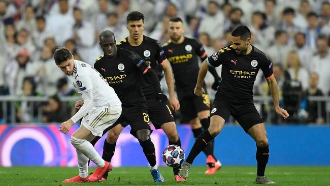 Real Madrid's Uruguayan midfielder Federico Valverde (L) challenges (From 2ndL) Manchester City's French defender Benjamin Mendy, Manchester City's Spanish midfielder Rodri and Manchester City's German midfielder Ilkay Gundogan during the UEFA Champions League round of 16 first-leg football match between Real Madrid CF and Manchester City at the Santiago Bernabeu stadium in Madrid on February 26, 2020. (Photo by OSCAR DEL POZO / AFP)