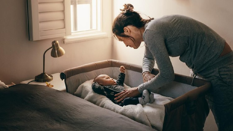 Mother putting her baby to sleep on a bedside baby crib. Woman bending forward over a crib to check her sleeping baby.