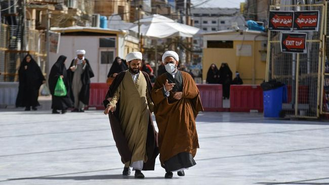 An Iraqi cleric wearing a protective mask walks alongside another in the central holy city of Najaf, on February 26, 2020. - Najaf is where Iraq confirmed its first novel coronavirus infection in an Iranian national studying in a Shiite seminary in the city, triggering widespread panic. (Photo by Haidar HAMDANI / AFP)