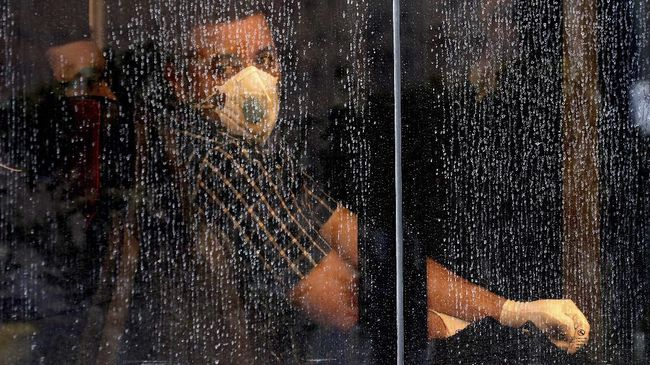 A commuter looks through a water-stained window wearing a mask and gloves to help guard against the Coronavirus, on a public bus in downtown Tehran, Iran, Sunday, Feb. 23, 2020. Iran's health ministry raised Sunday the death toll from the new virus to 8 people in the country, amid concerns that clusters there, as well as in Italy and South Korea, could signal a serious new stage in its global spread. (AP Photo/Ebrahim Noroozi)