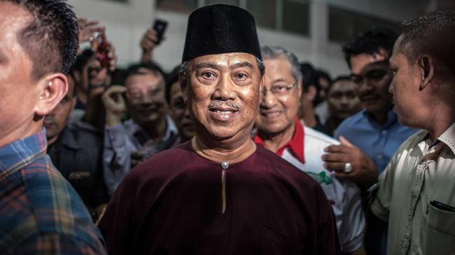 This picture taken on December 7, 2015 shows Malaysia's former deputy prime minister and deputy president of the United Malays National Organisation (UMNO) Muhyiddin Yassin (C) and Malaysia's former prime minister Mahathir Mohammad (Back C) arriving for a rally after Muhyiddin was barred from speaking ahead of the UMNO's annual general assembly in Kuala Lumpur. The ruling party UMNO's five day general assembly 2015 with the official opening by the party President Najib Razak will start from December 8-12. AFP PHOTO / MOHD RASFAN (Photo by MOHD RASFAN / AFP)