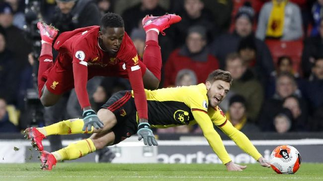 Liverpool's Divock Origi, left, duels for the ball with Watford's Kiko Femenia during the English Premier League soccer match between Watford and Liverpool at Vicarage Road stadium, in Watford, England, Saturday, Feb. 29, 2020. (AP Photo/Alastair Grant)