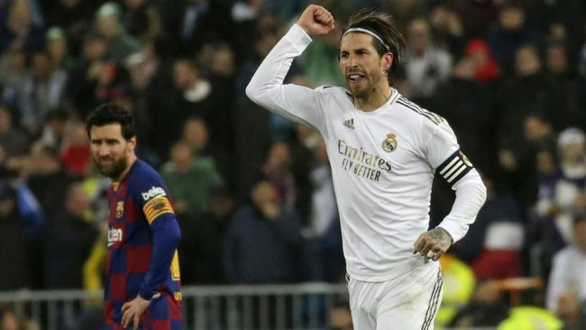 Real Madrid's Sergio Ramos celebrates as he runs past Barcelona's Lionel Messi during the Spanish La Liga soccer match between Real Madrid and Barcelona at the Santiago Bernabeu stadium in Madrid, Spain, Sunday, March 1, 2020. (AP Photo/Andrea Comas)