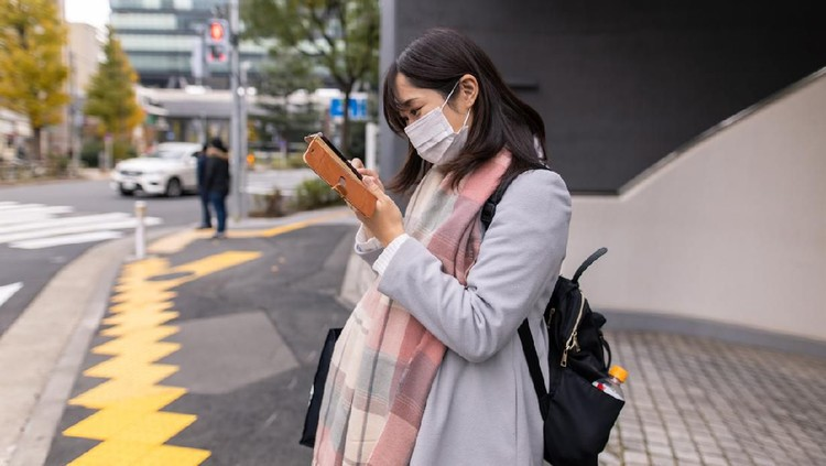 Asian pregnant Woman She is in the middle of the road Wear a PM2.5 dust mask.