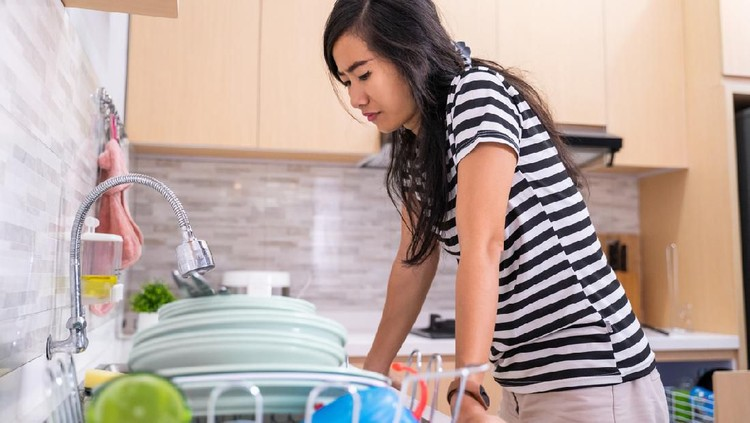frustrated woman hate to wash the dish in the kitchen sink