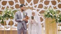 <p>Tak kuasa menahan rasa bahagia, Hawaariyyun dan Dena tersenyum sambil menunjukkan buku nikah. (Foto: Instagram @benzoitubejo)</p>