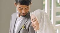 <p>Dena tampil cantik dibalut gaun putih, sedangkan Hawaariyyun rapih dengan setelan jas abu-abu dan kemeja putih. (Foto: Instagram @hijazpictura)</p>