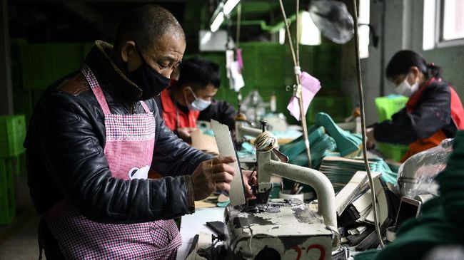 This photo taken on February 27, 2020 shows workers wearing face masks as they make insoles at the Zhejiang Xuda Shoes Co. factory in Wenzhou. - The number of new cases of the COVID-19 coronavirus in China has declined in recent days, but infections in other countries have gathered pace. (Photo by NOEL CELIS / AFP)