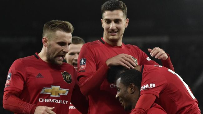 Manchester United's Odion Ighalo, front down, celebrates with teammates after scoring his side's second goal during the FA Cup fifth round soccer match between Derby County and Manchester United at Pride Park in Derby, England, Thursday, March 5, 2020. (AP Photo/Rui Vieira)