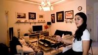 <p>Ruang keluarga rumah bernuansa monokrom, dipenuhi lukisan yang membuat ruangan terlihat elegan. (Foto: YouTube channel Adiez Gilang)</p>