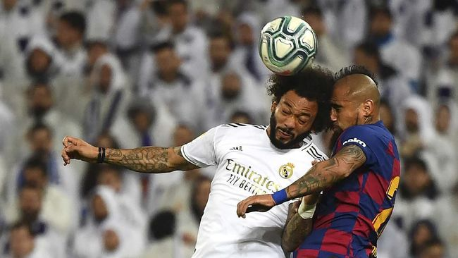 Barcelona's Chilean midfielder Arturo Vidal (R) heads the ball with Real Madrid's Brazilian defender Marcelo during the Spanish League football match between Real Madrid and Barcelona at the Santiago Bernabeu stadium in Madrid on March 1, 2020. (Photo by GABRIEL BOUYS / AFP)